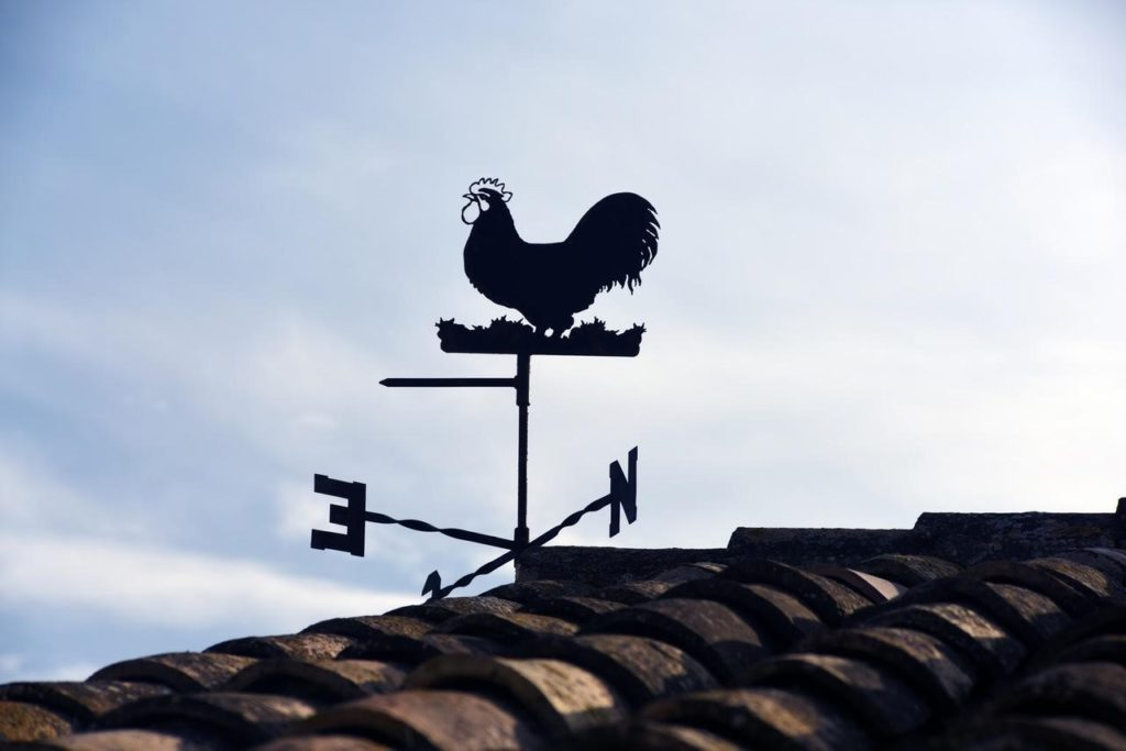 wind blowing a weathervane on top of a roof